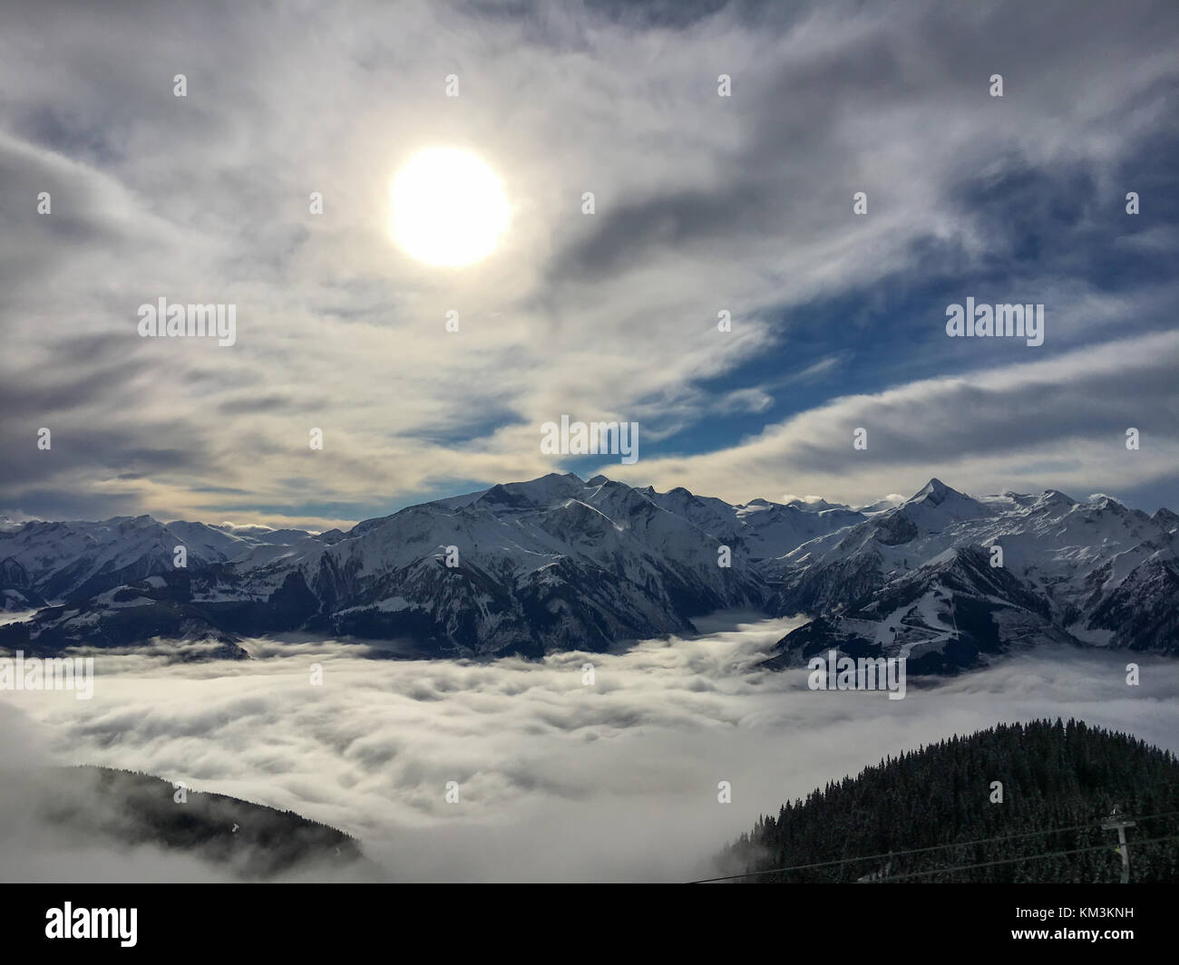 A blanket of clouds is lying over Lake Zell on a sunny winter day in the Austrian alps Stock Photo