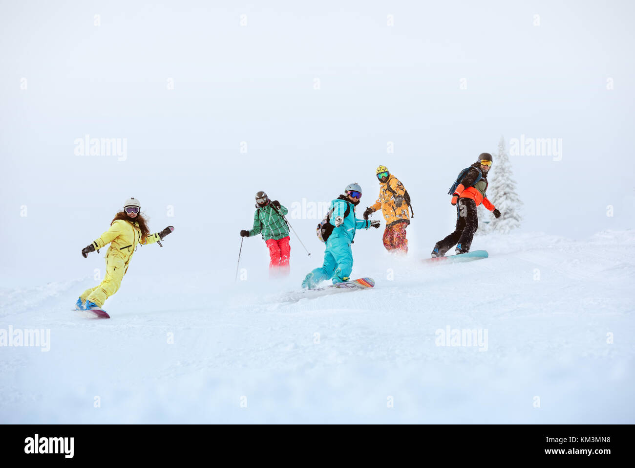 Group of happy snowboarders and skiers on ski slope - Stock Image