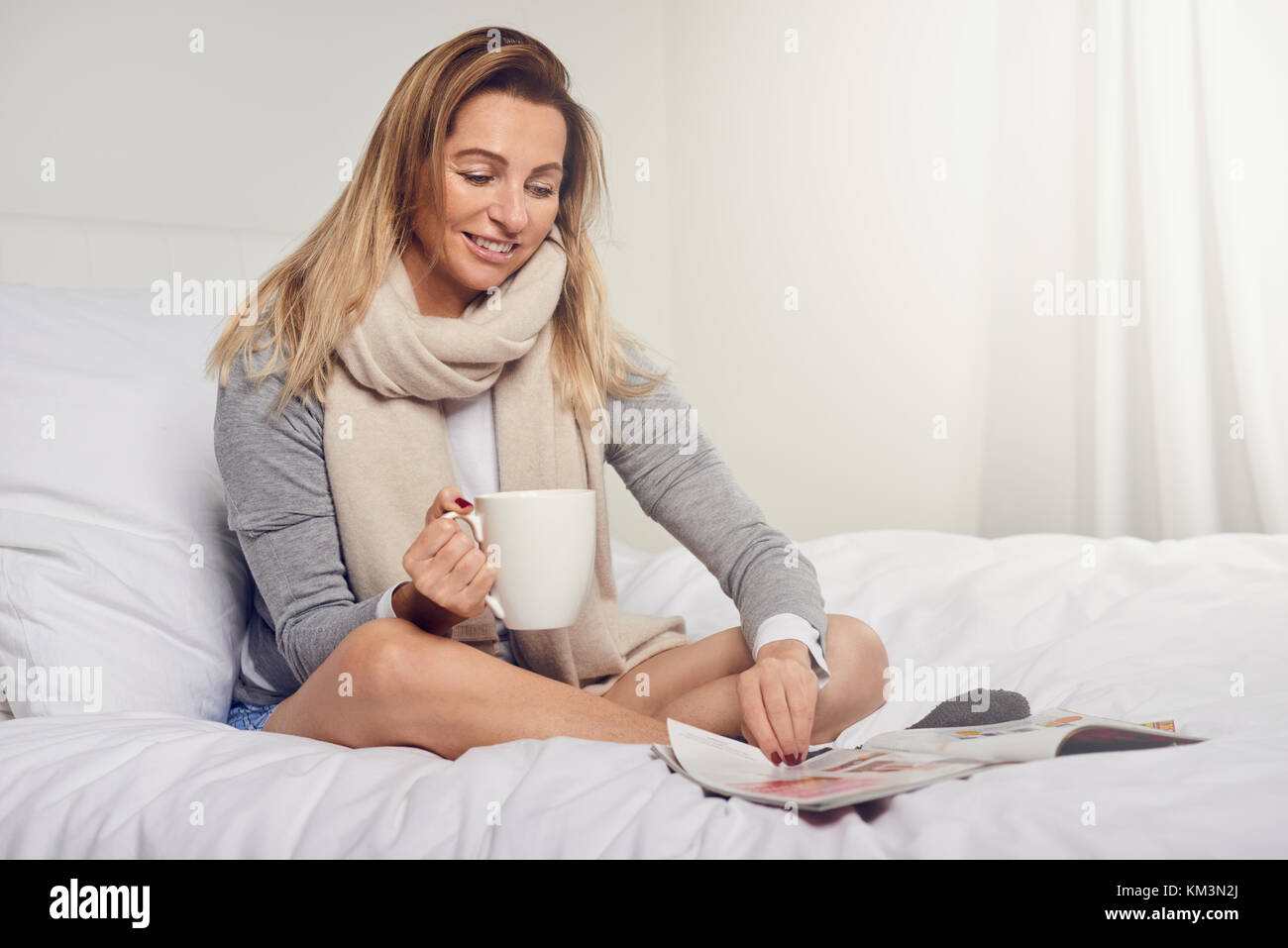 Attractive smiling contented young woman reading a magazine as she relaxes barefoot on her bed with a mug of coffee - Stock Image