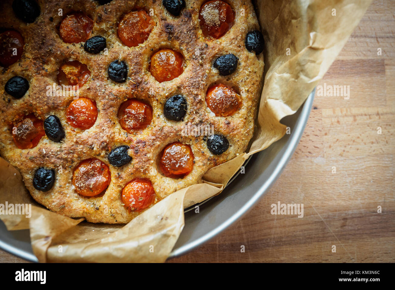 Close up of a typical Apulian focaccia in a tin tray on a wooden board. Flat lay. Landscape format. - Stock Image