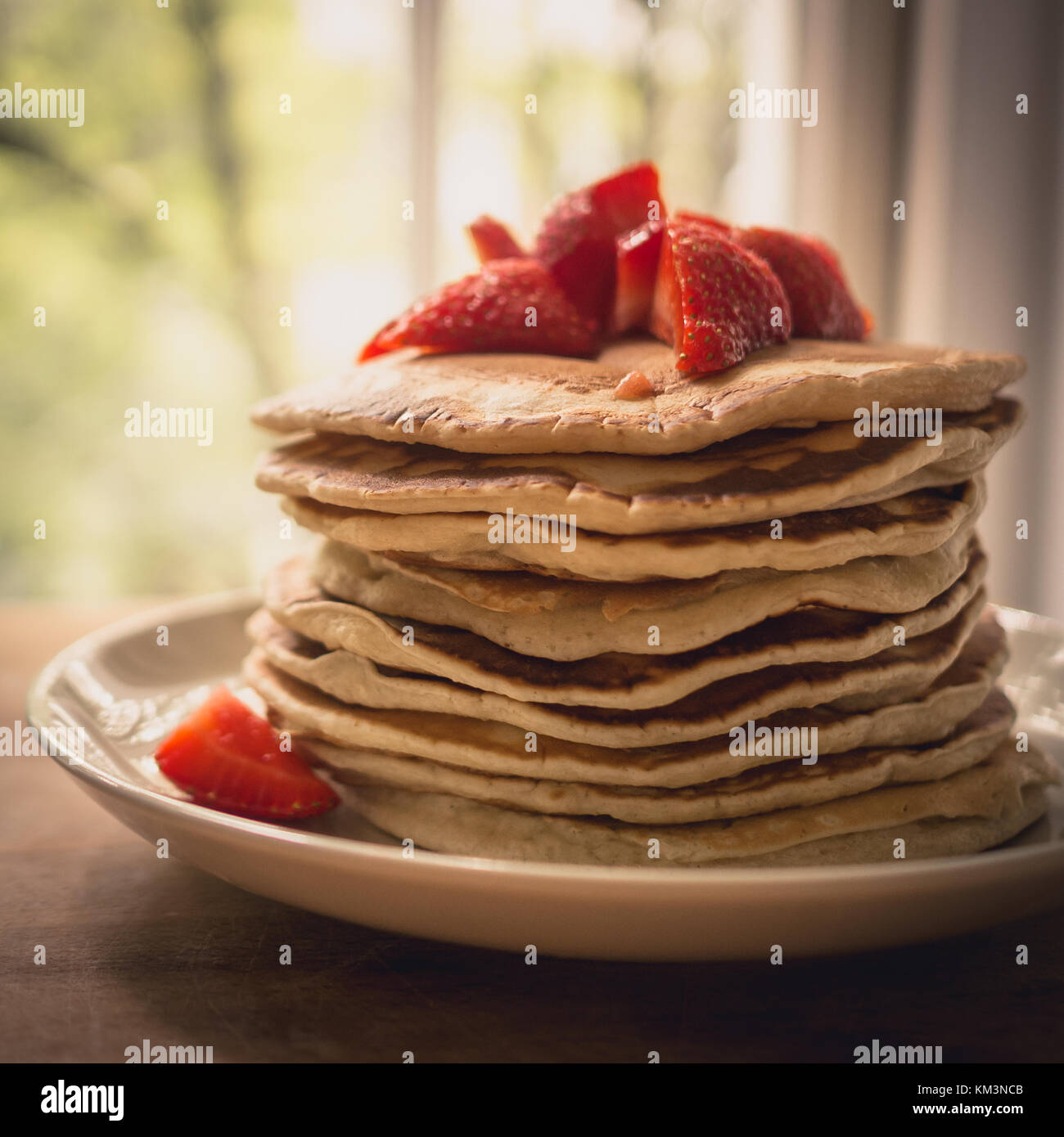 Close up of a stack of homemade pancakes on a white plate with cut strawberries and maple syrup on top. Stock Photo