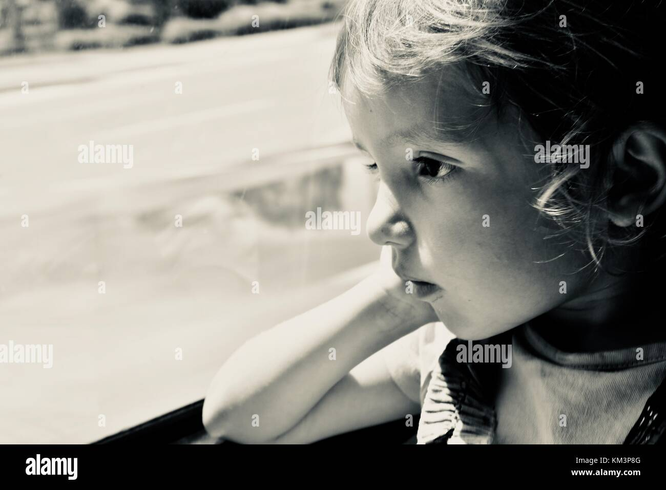 Young girl sitting on a bus looking out the window thinking, Townsville, Queensland, Australia - Stock Image