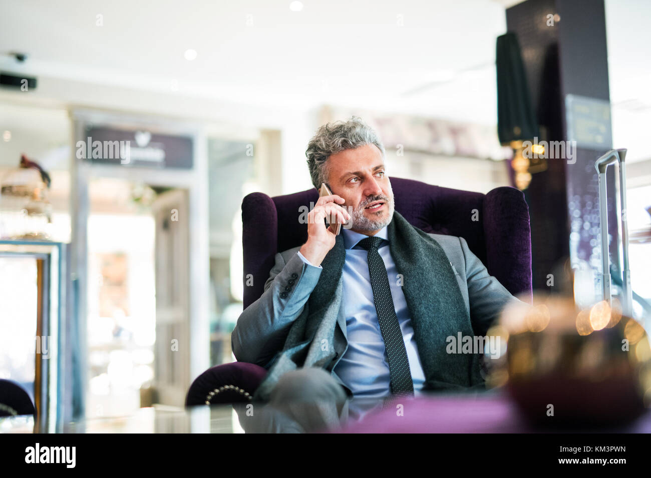 Mature businessman with smartphone in a hotel lounge. - Stock Image