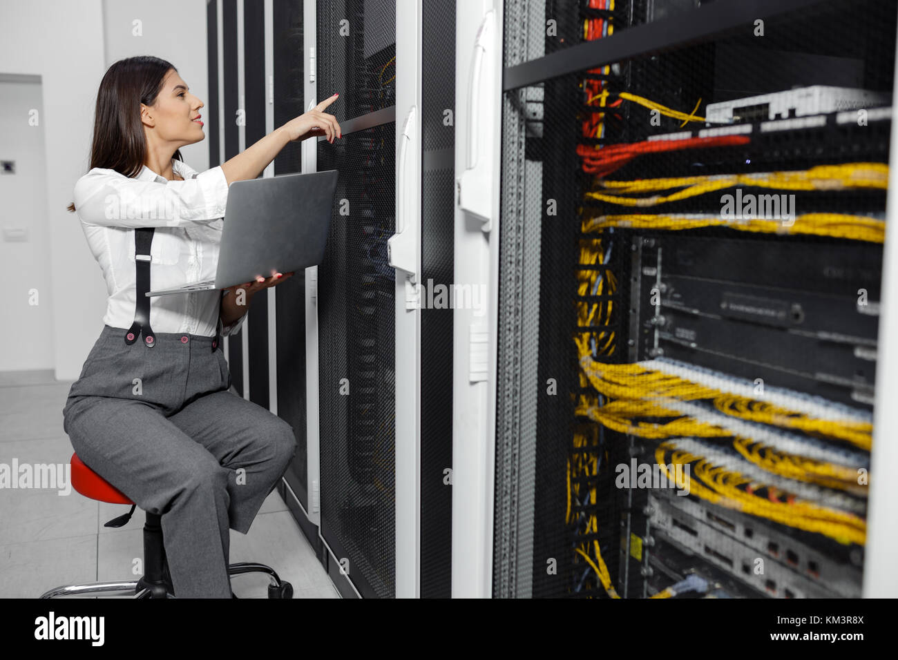 Portrait of technician working on laptop in server room - Stock Image