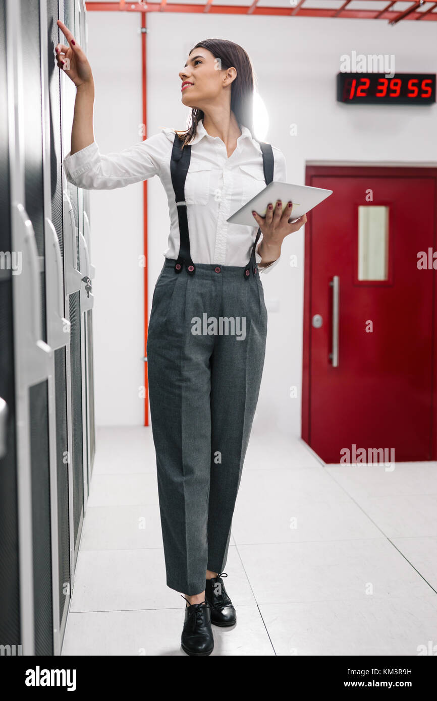 Technician using tablet pc while analysing server in large data center - Stock Image