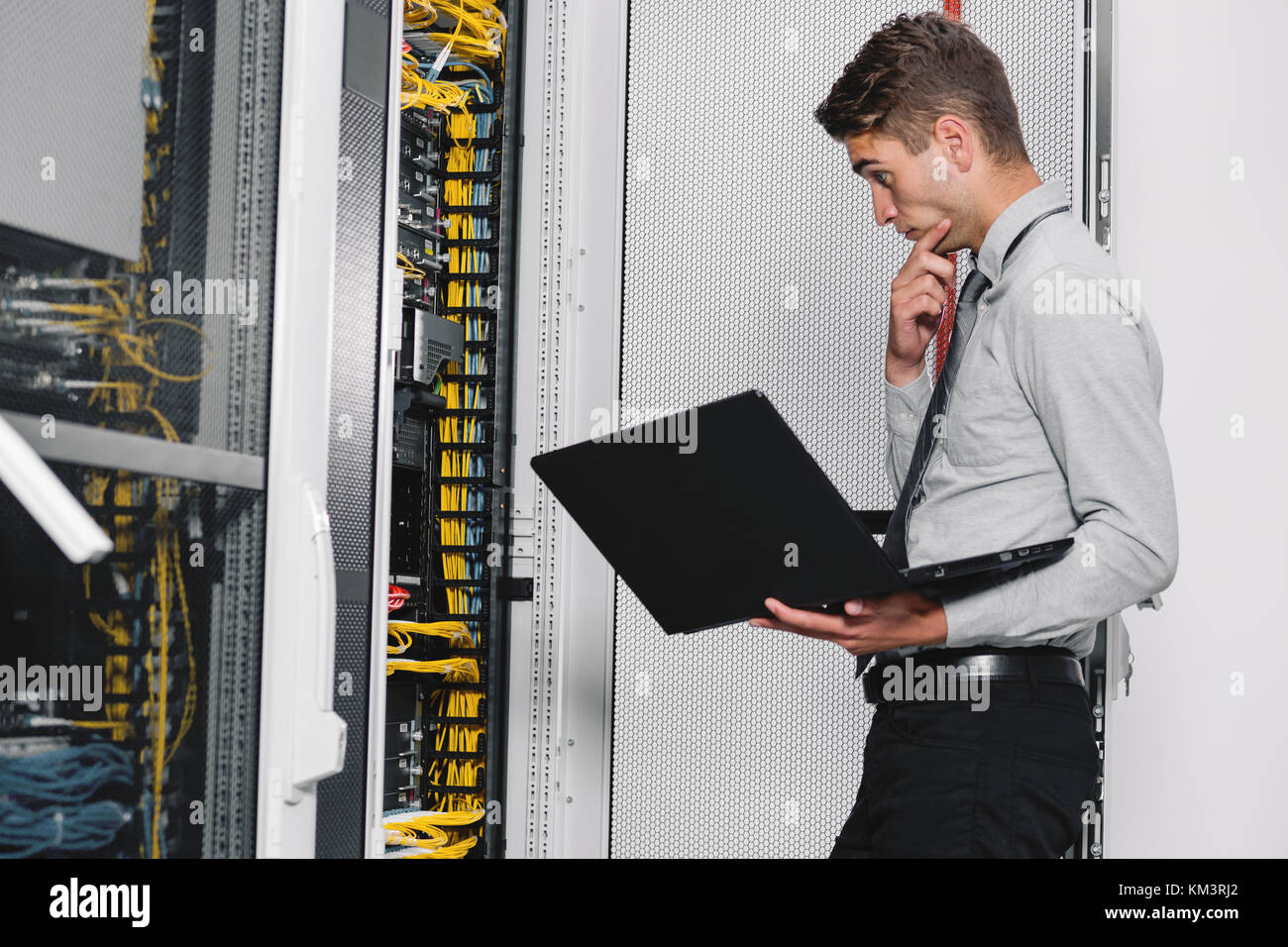 Portrait of modern young man holding laptop standing in server room working with supercomputer - Stock Image