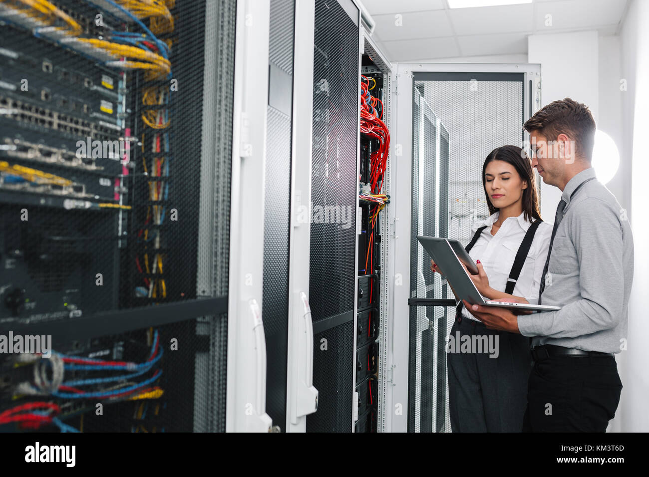 Team of technicians working together on servers at the data centre Stock Photo
