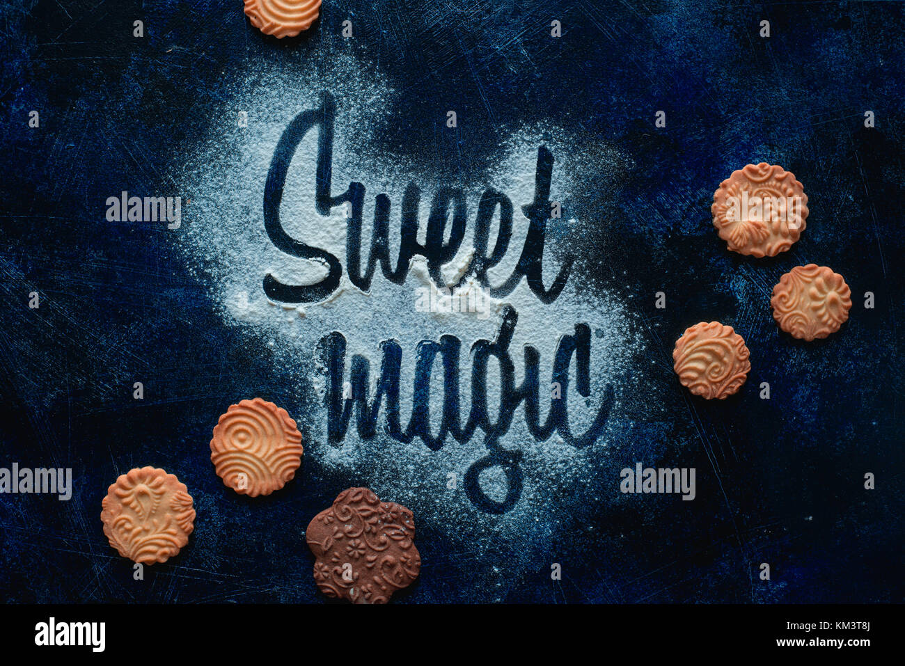 Words Sweet Magic made with flour. Cookies and sugar powder on a dark background. Food typography concept. Sweet flat lay. Stock Photo