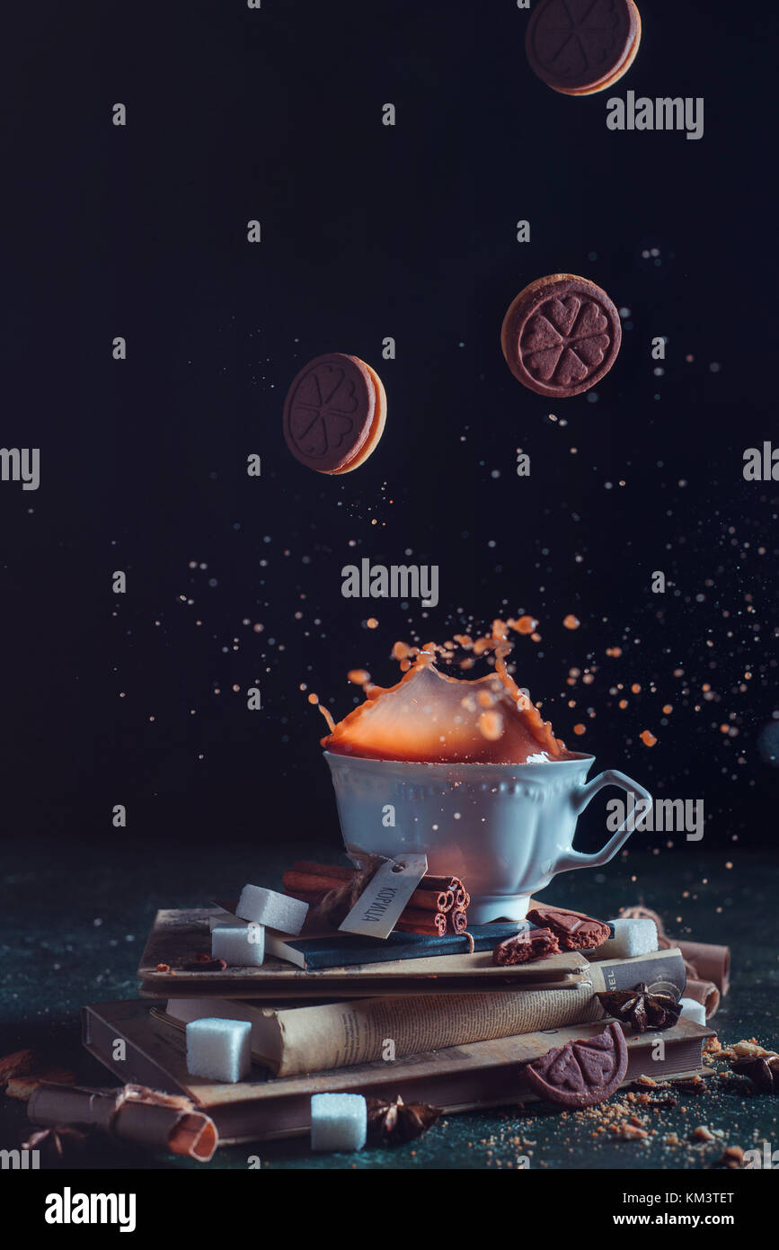 Porcelain tea cup with falling cookies and a splash on a dark background. Frozen motion food photography. - Stock Image
