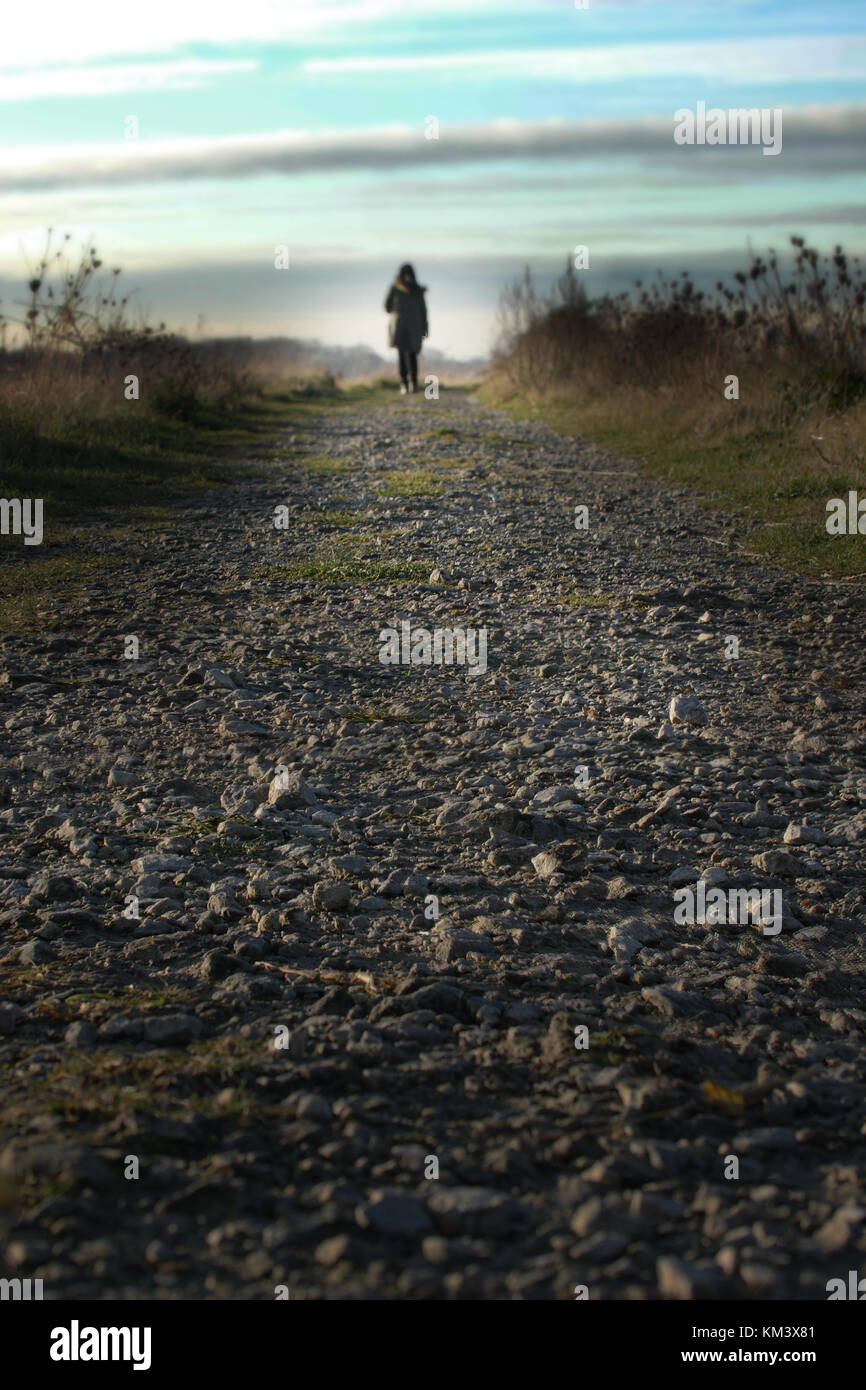 Walking a path into the distance. Back view of a woman on the horizon at the end of a path. - Stock Image