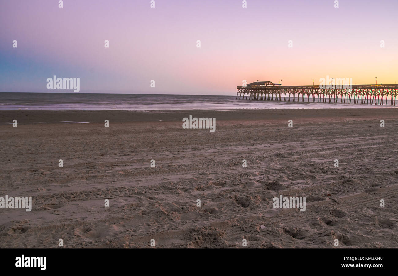 Myrtle Beach, South Carolina Beach. Seascape in Myrtle Beach, South Carolina with long wooden pier and sunset horizon - Stock Image