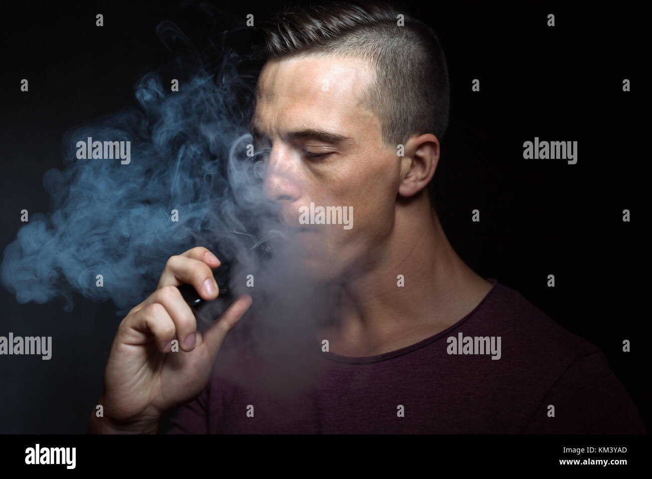 Men on black background vaping and releases a cloud of vapor. - Stock Image
