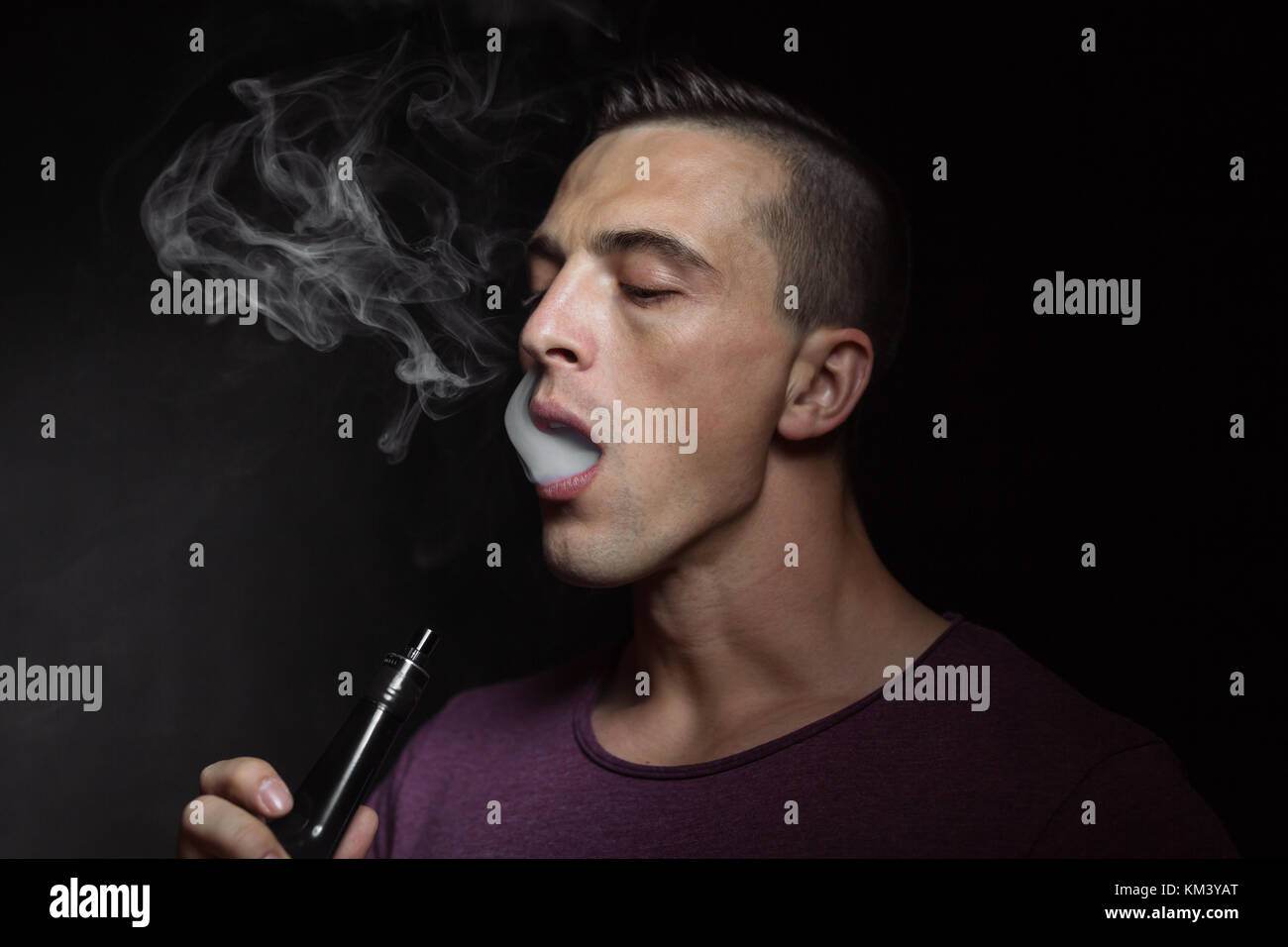Man on black background vaping and releasing a cloud. - Stock Image