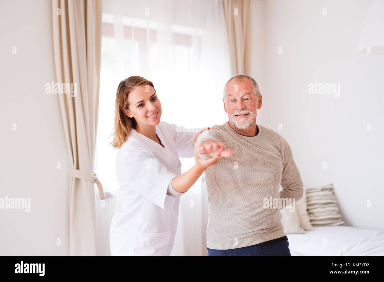 Health visitor and senior man during home visit. - Stock Image