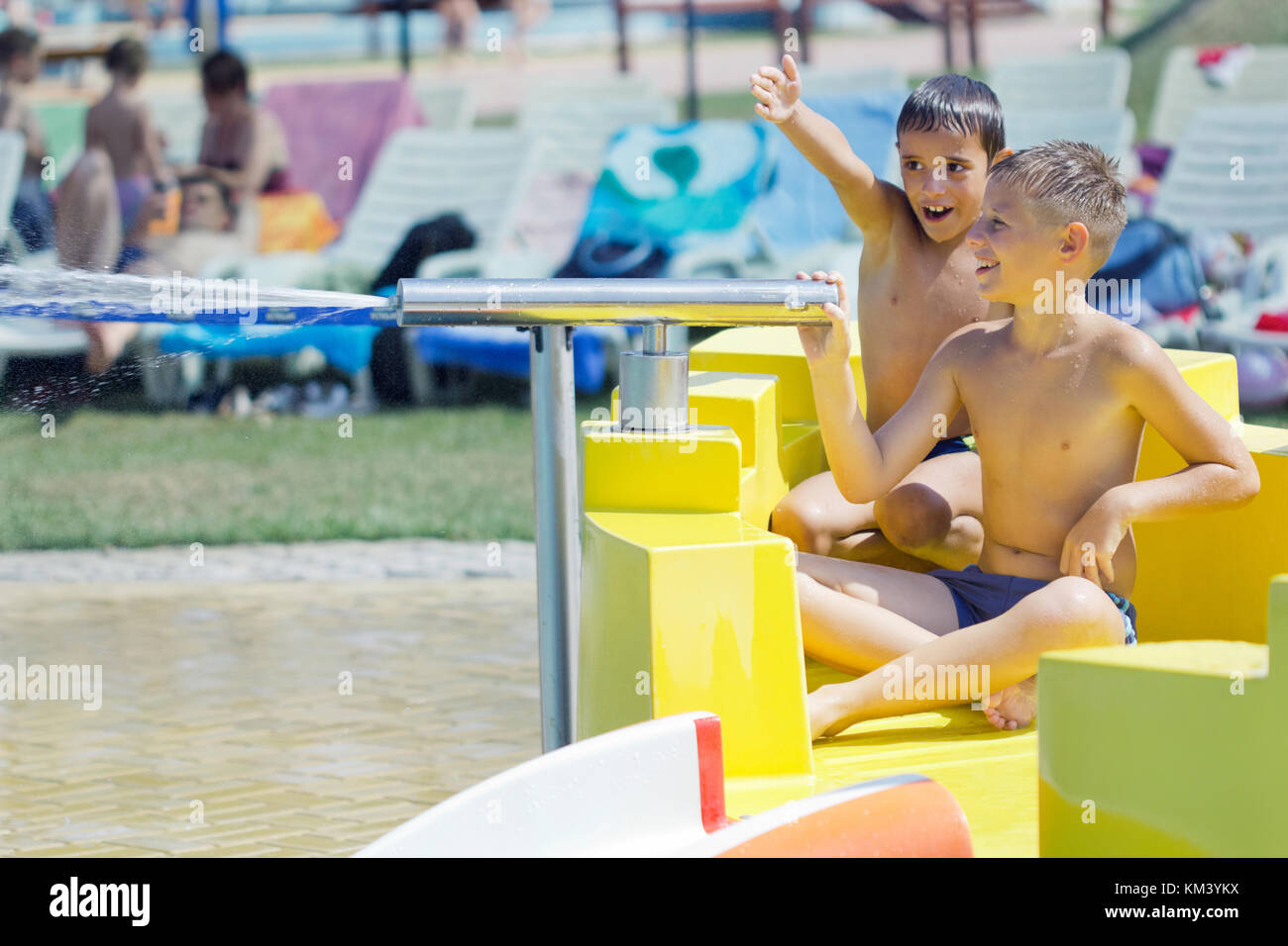 little boys having fun in aquapark with water cannon - Stock Image