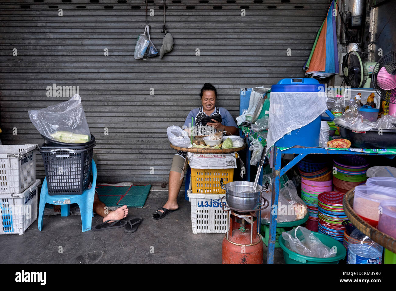 Funny and humorous Thailand street scene with protruding leg of a man asleep - Stock Image