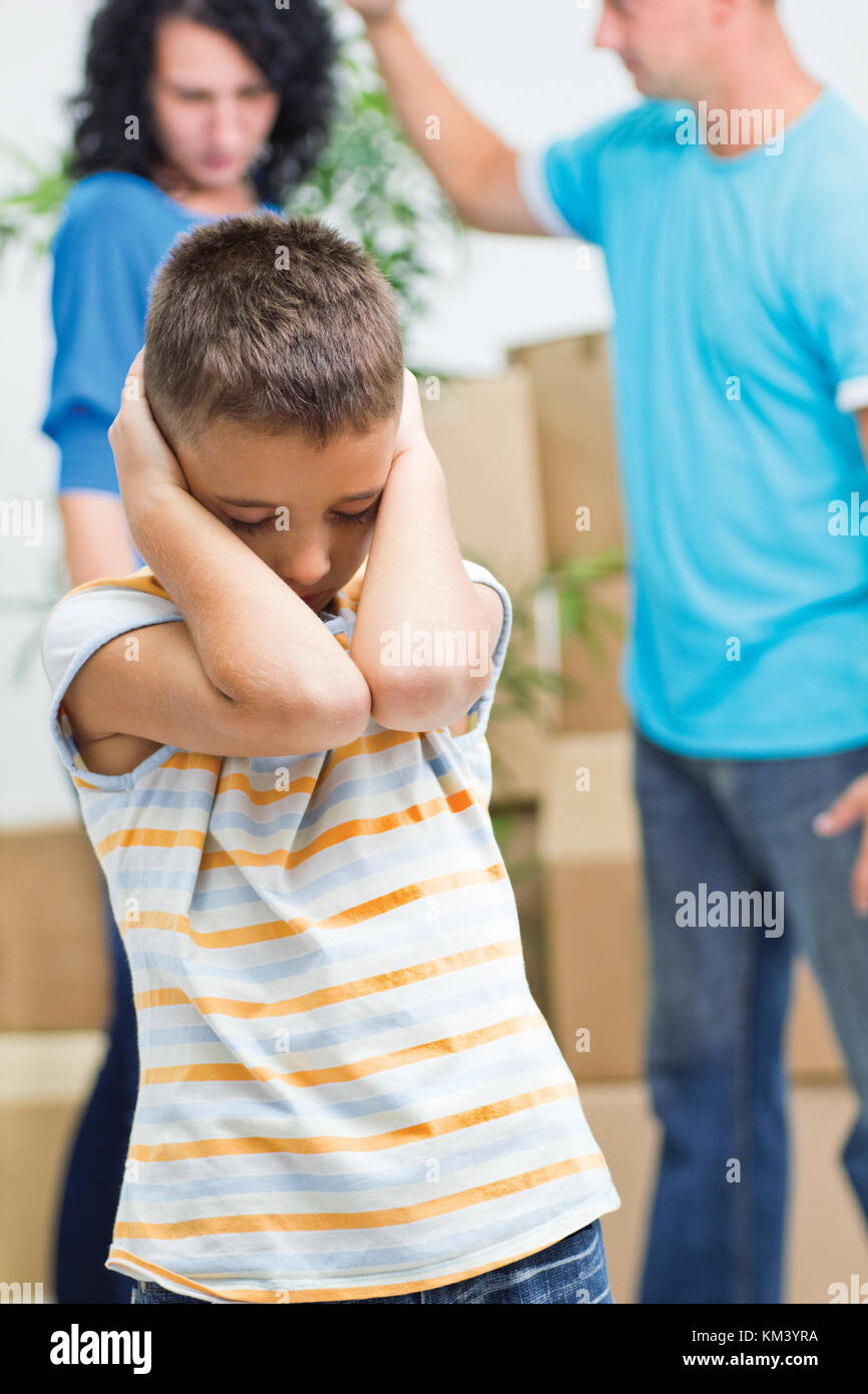 young boy agonizes while parents figh - Stock Image