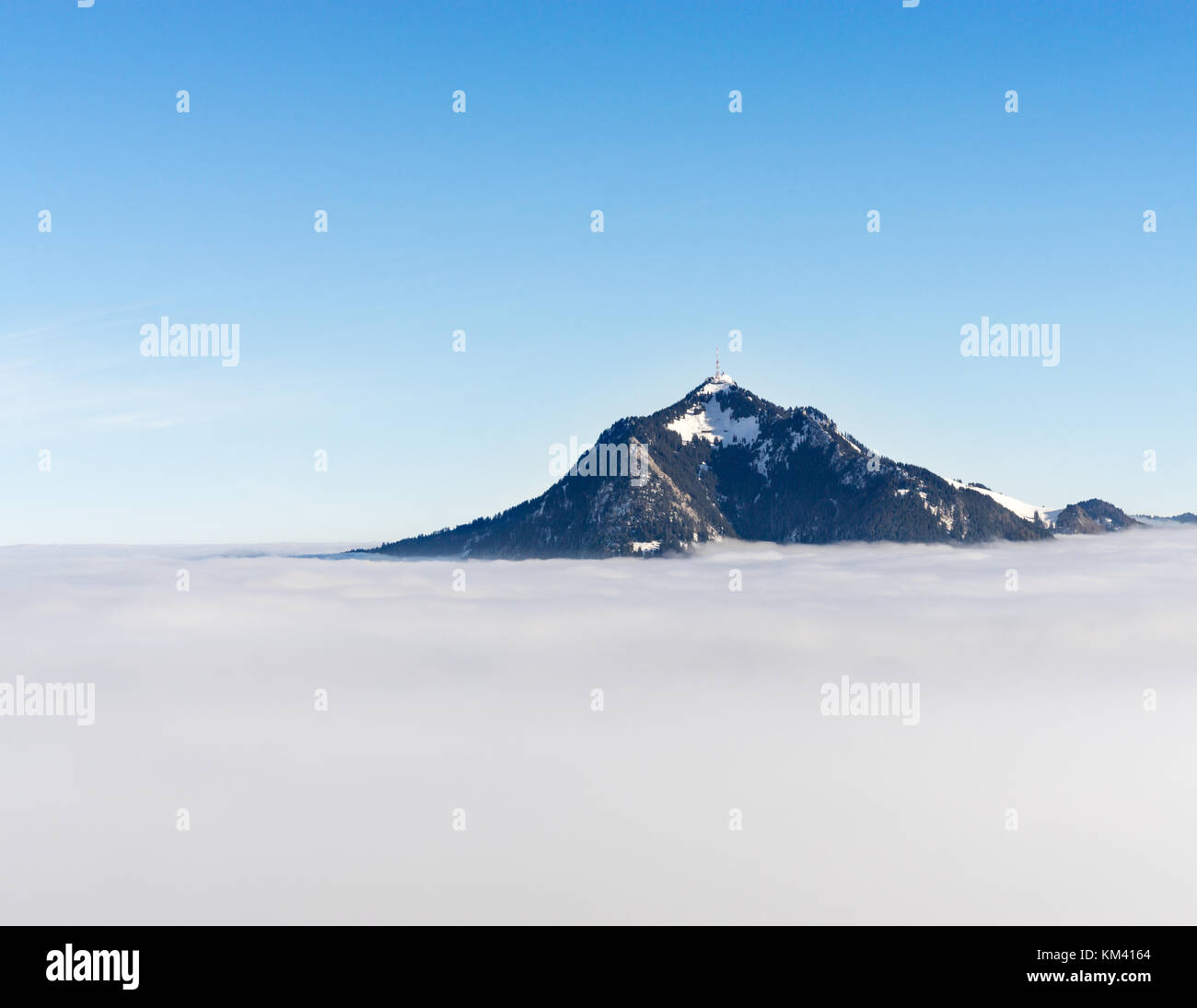 Mountain stick out of foggy cloud layer. Gruenten, Bavaria, Germany. Foresight and vision for business concept and Stock Photo
