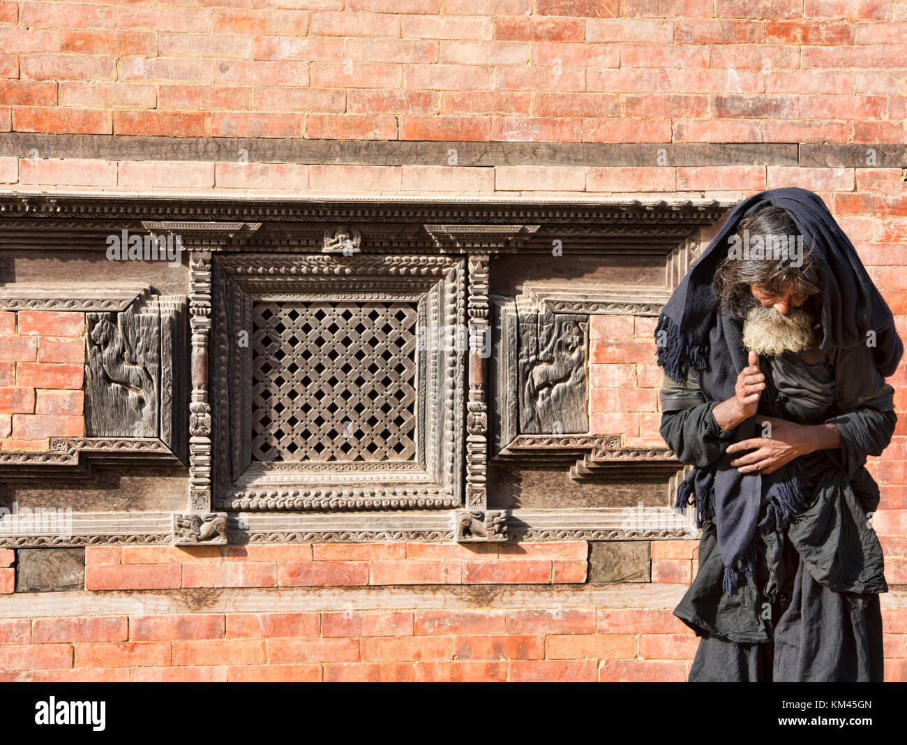 Homeless man in the UNESCO temples of Bhaktapur, Nepal - Stock Image