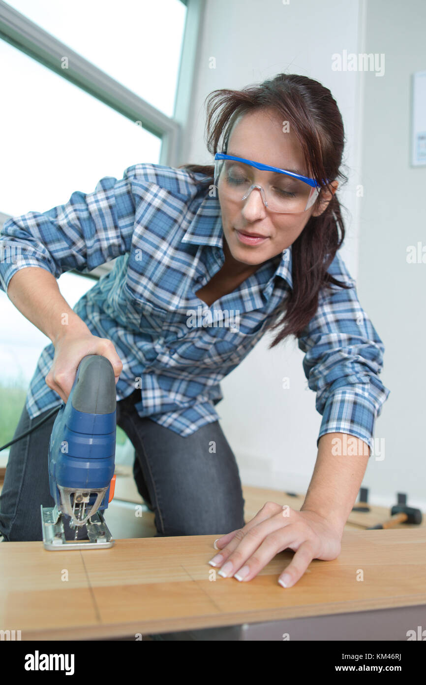 woman cutting a plank using an electric cutter - Stock Image