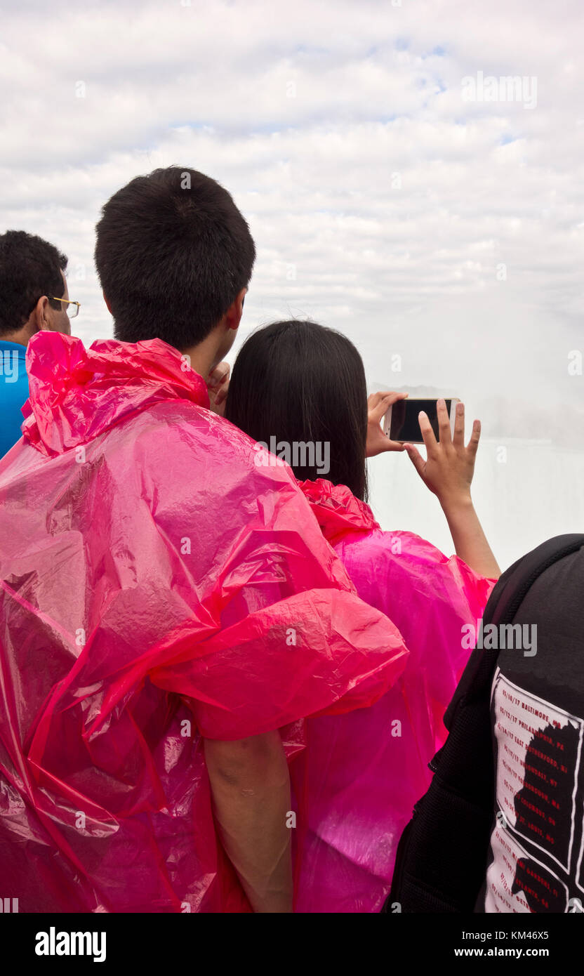 Young Asian couple in Niagara Falls Canada taking cell phone photos of the Horseshoe Falls. Tourists. Stock Photo