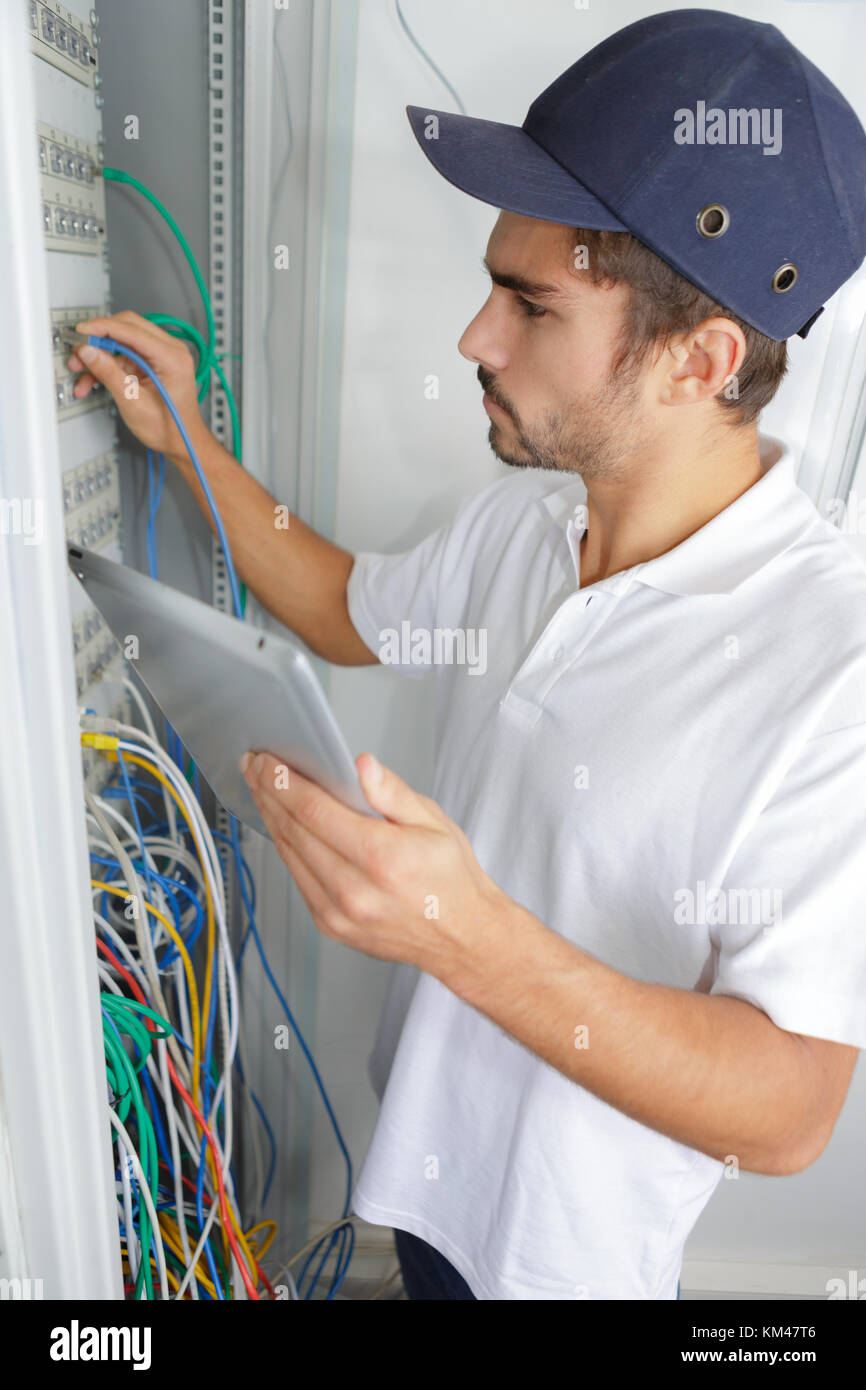 focused electrician applying safety procedure while working on Stock ...