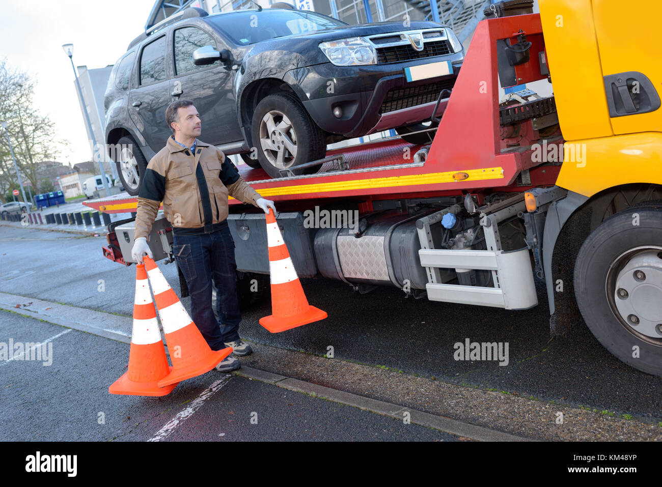 a tow truck takes away a broken car - Stock Image