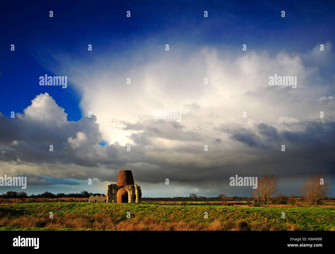 A view of heavy shower clouds over the Ruins of St Benet's Abbey gatehouse and drainage mill at Horning, Norfolk, - Stock Image