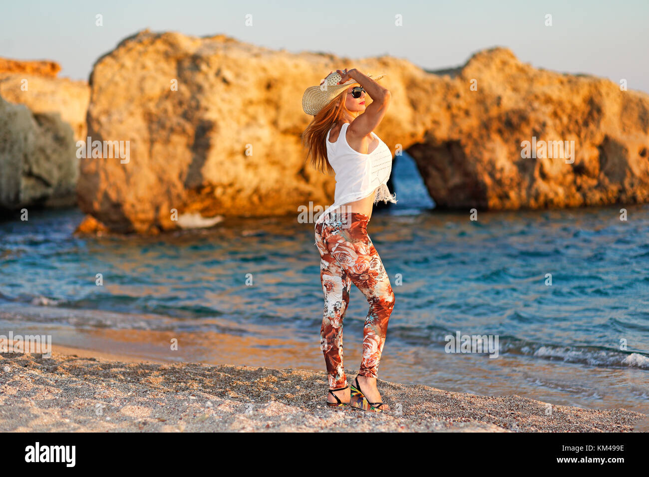 A beautiful woman at a wild beauty beach with unique caves in Karpathos, Greece - Stock Image