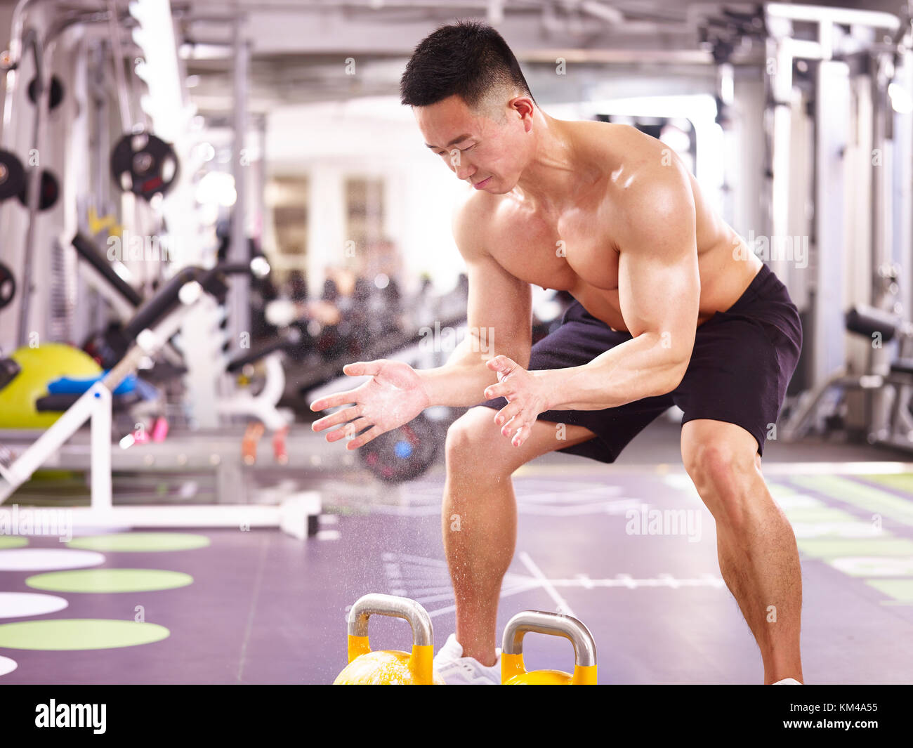 asian male bodybuilder working out in gym using kettle bells. - Stock Image