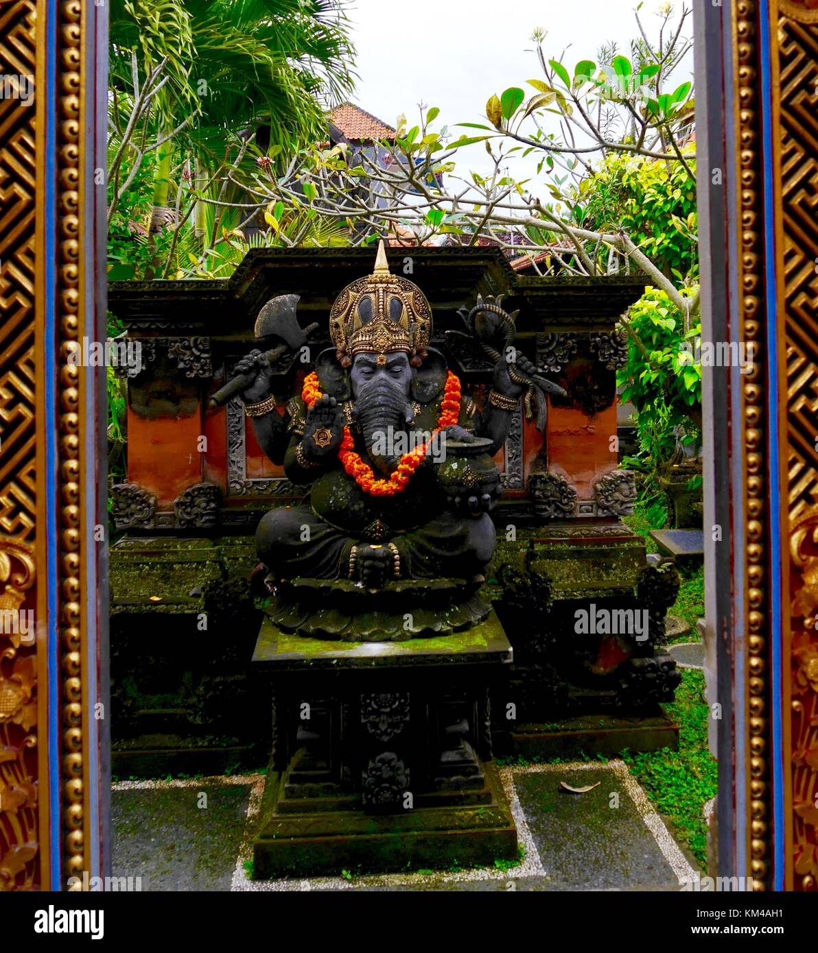 Vertical shot of statue of elephant-headed Hindu god Ganesha (Ganesh) with marigold garland in leafy temple garden, Stock Photo