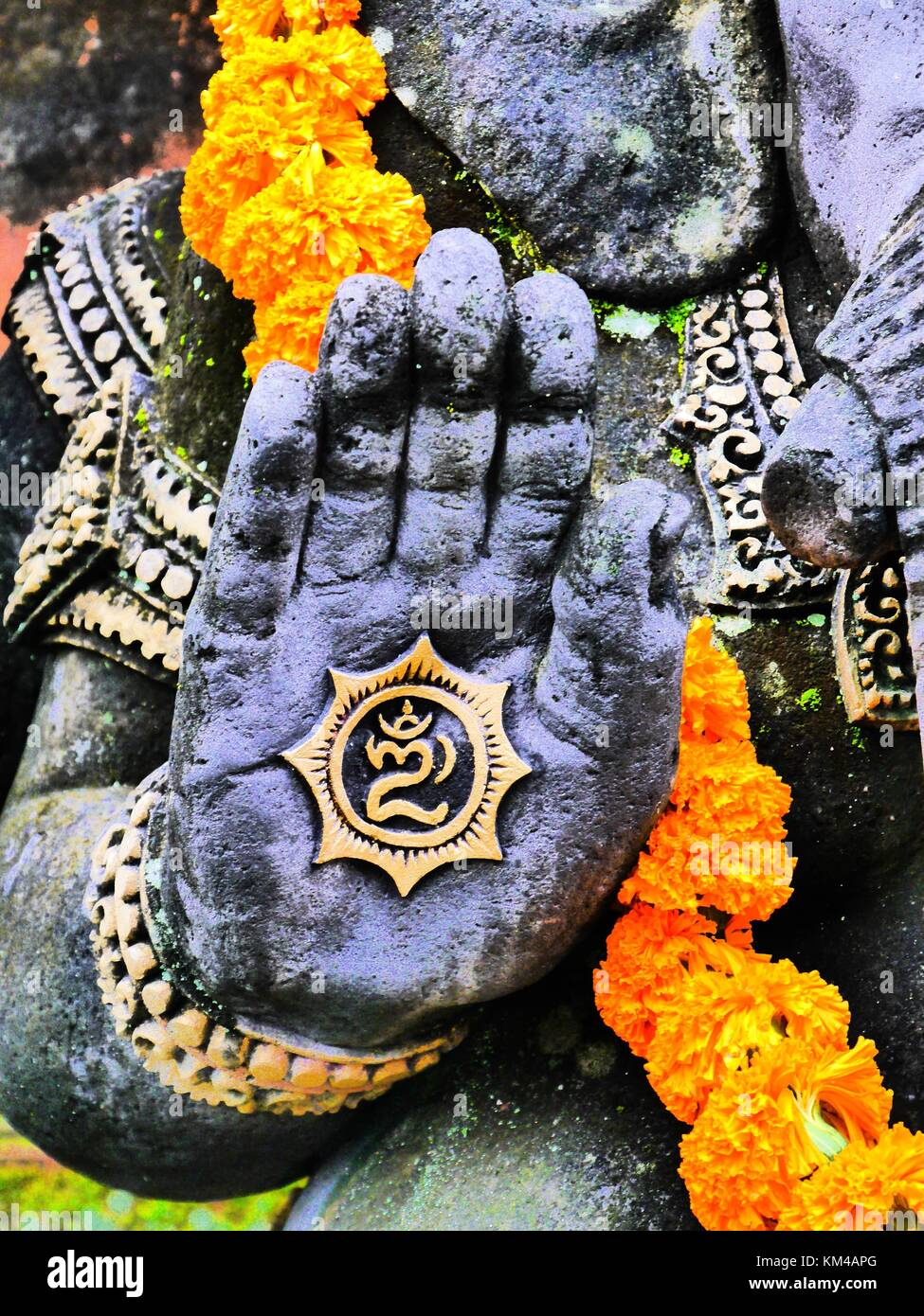 High contrast close up of hand of statue of elephant-headed Hindu god Ganesha (Ganesh) with marigold garland in Stock Photo