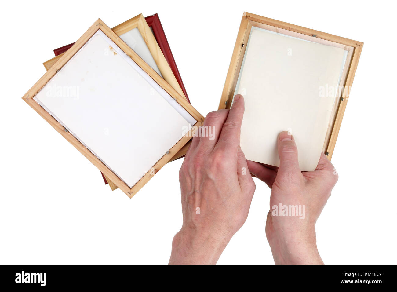 Old man grandfather inserts photos into wooden photo frames. Nostalgia by youth  concept.Isolated on white top view - Stock Image