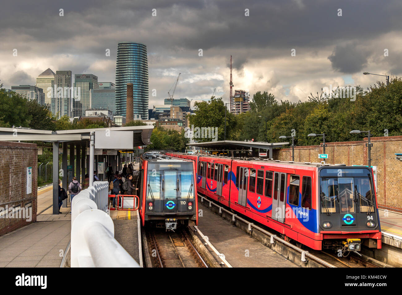 Rail Passengers board a Dockland's Light Railway Train at Mudchute DLR Station with the towers of Canary Wharf - Stock Image