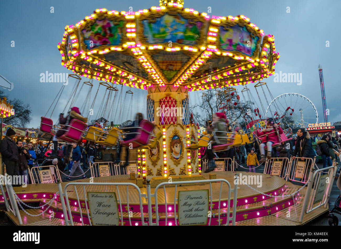 A chair-o-planes ride for young children at a fairground at sunset. - Stock Image
