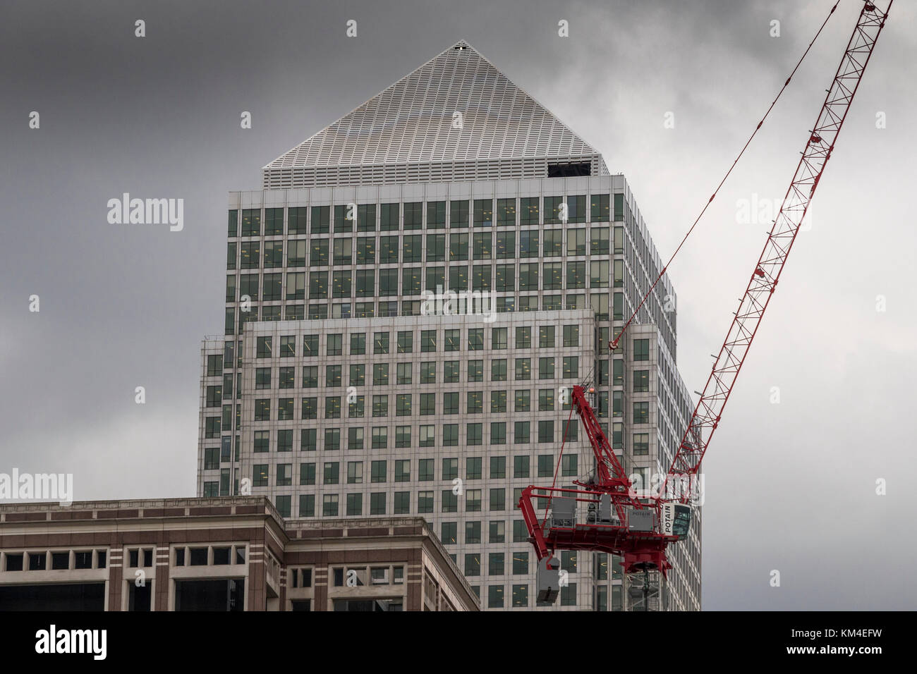 A construction site crane at work overlooked by  The Giant tower of One Canada Square ,Canary Wharf , Docklands, - Stock Image