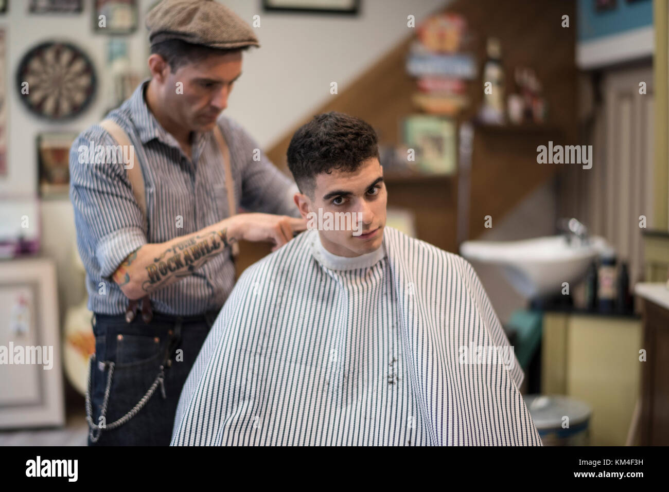 Barber shop, man cuts person hair - Stock Image