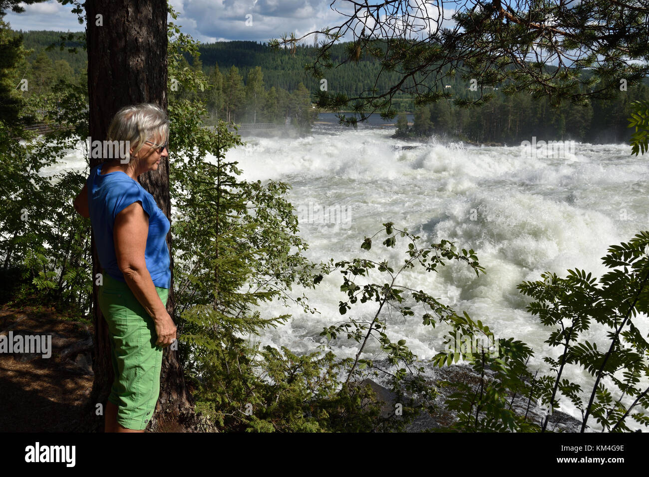 Women standing next to a tree looking down to white water, picture from Bredsel in the North of Sweden. - Stock Image
