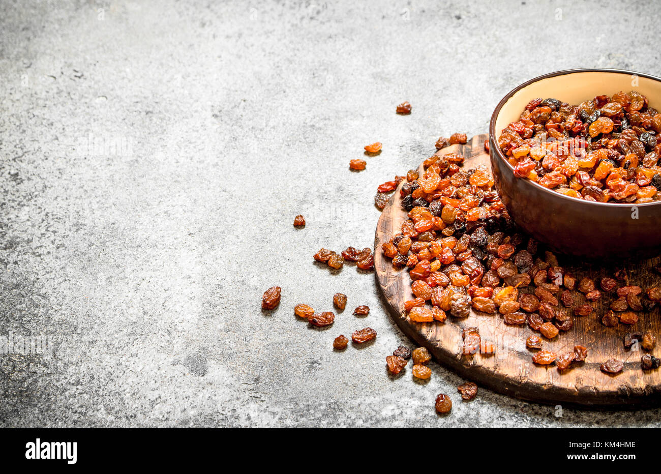 Raisins in a bowl. On rustic background . - Stock Image