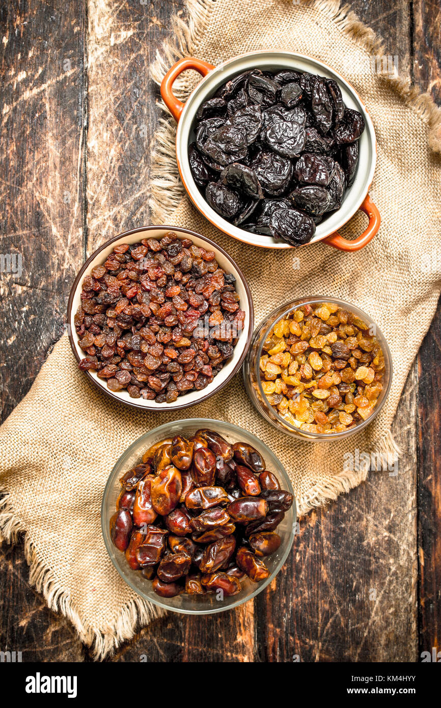 Different dried fruit in bowls. On wooden background. - Stock Image