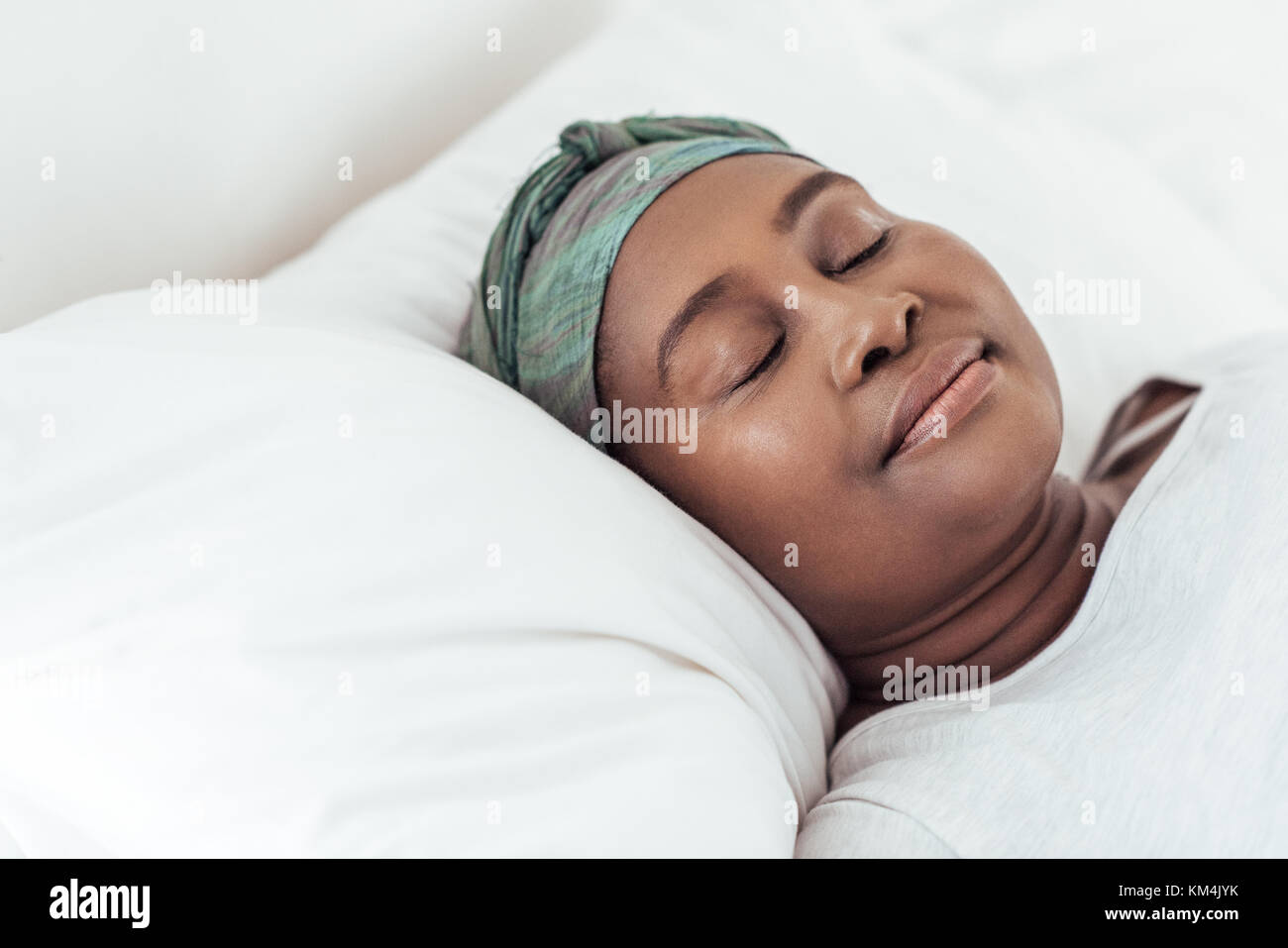 Young African woman wearing a headscarf asleep in bed - Stock Image