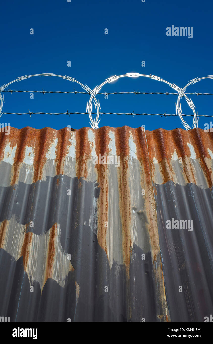 Low angle view of worn corrugated metal fence, razor wire