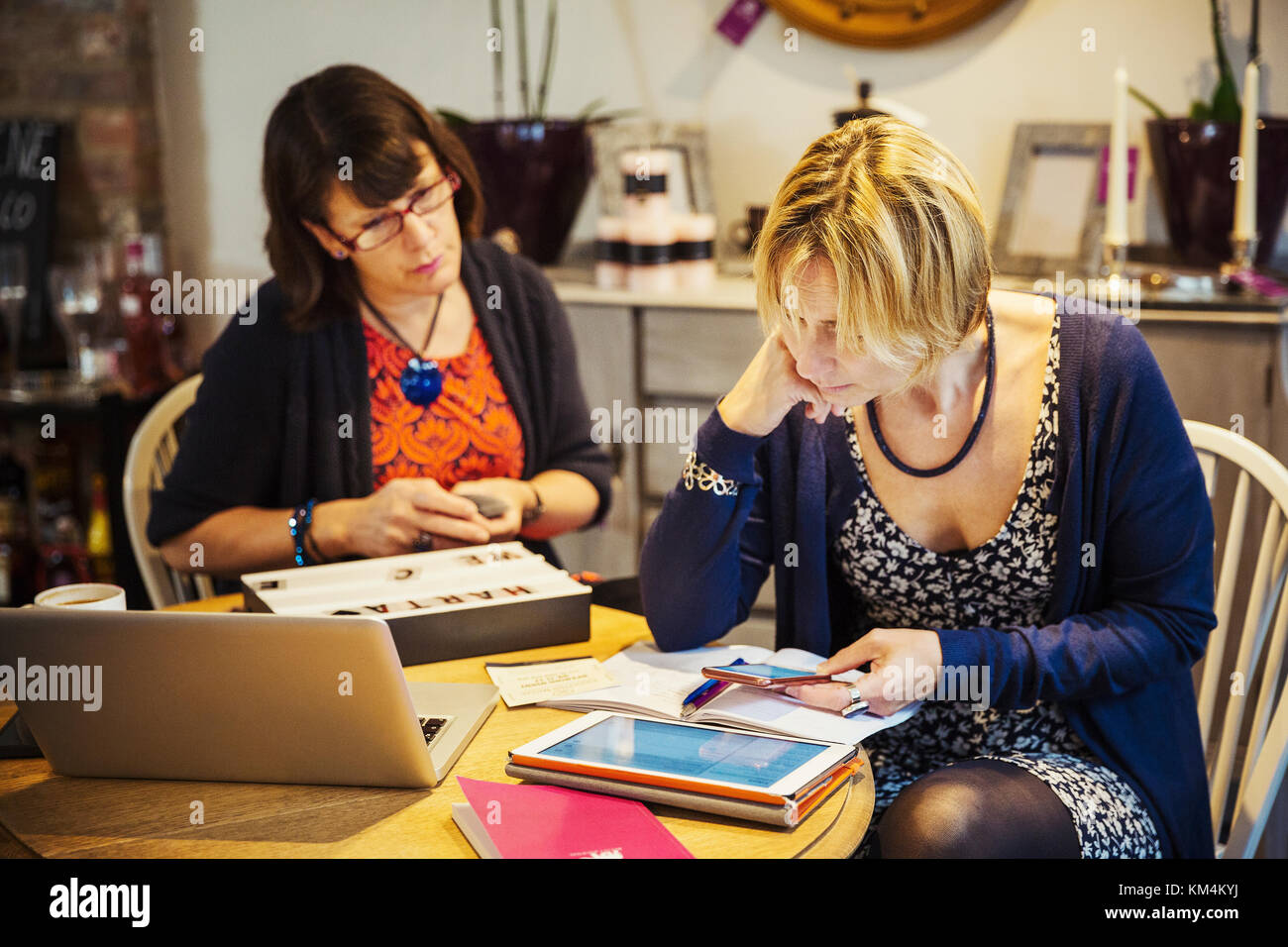 Two women seated at a table, one using a smart phone looking at a laptop screen. - Stock Image
