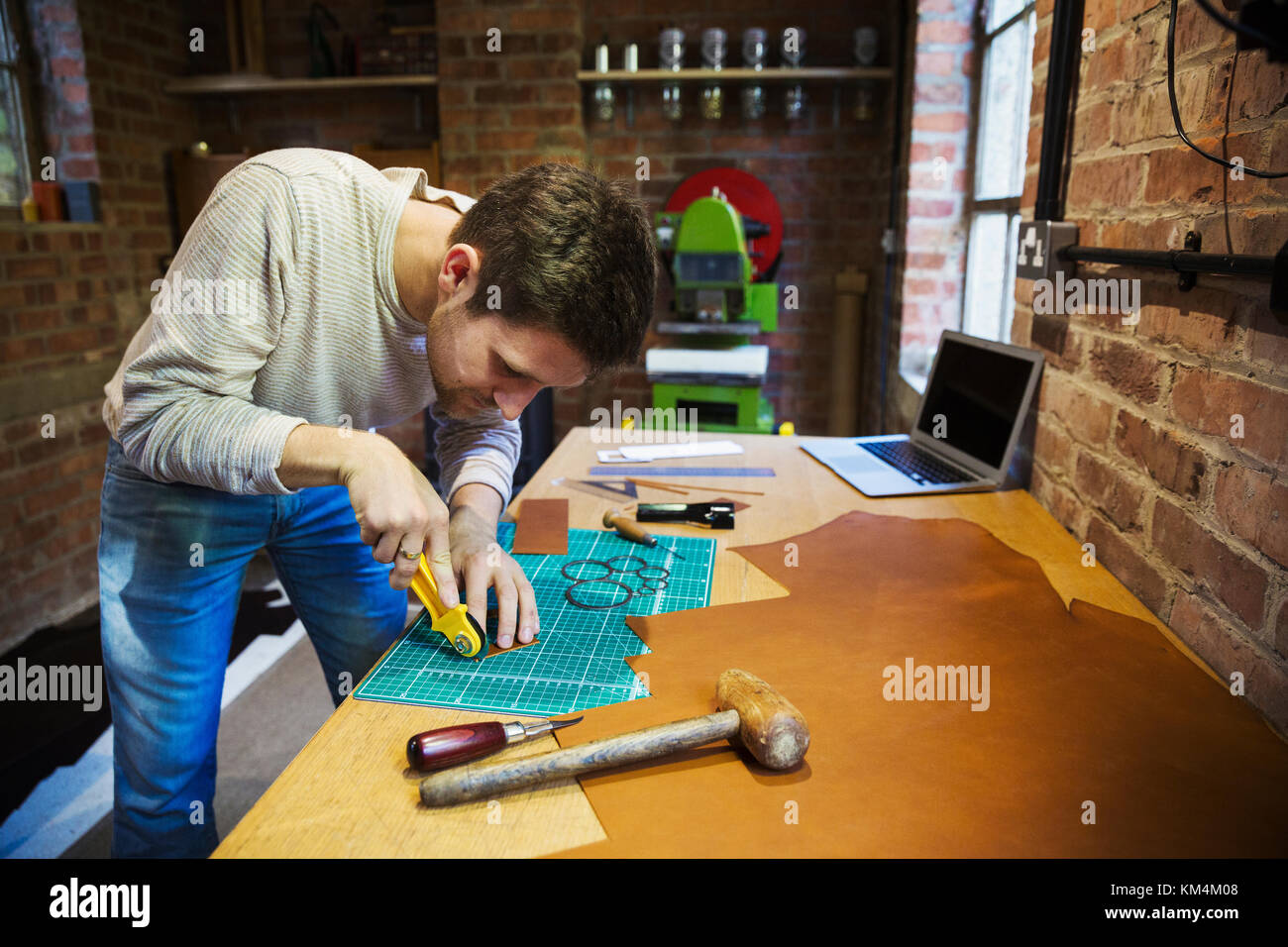 A craftsman using a rotary cutter wheel on a cutting mat on a small piece of brown leather. - Stock Image