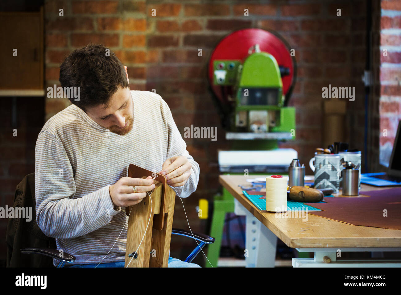 A craftsman in a workshop, threading cord or twine through a small handmade object. - Stock Image