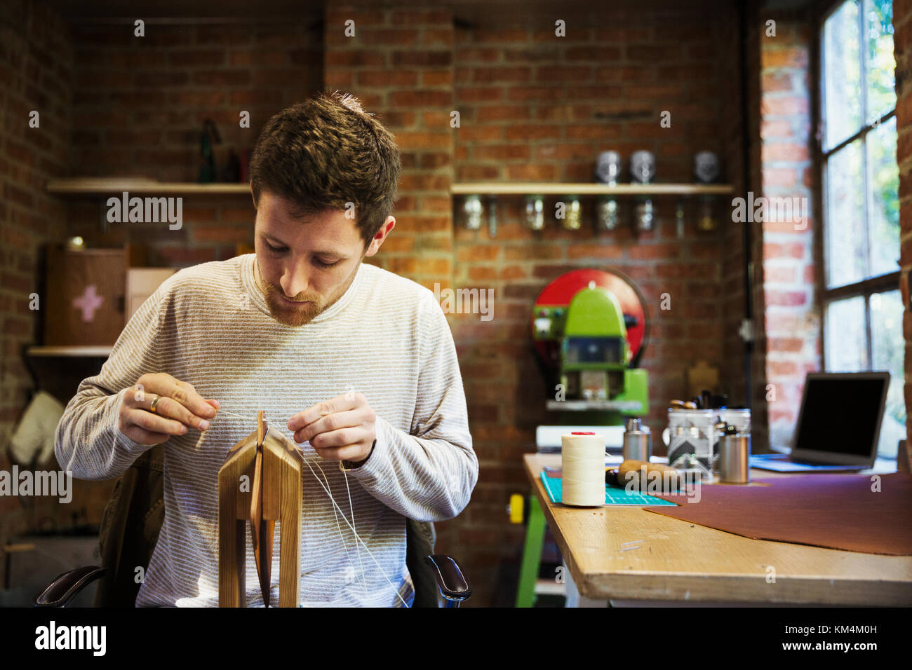 A craftsman seated at a bench in a small workshop, threading string through a wooden object. - Stock Image