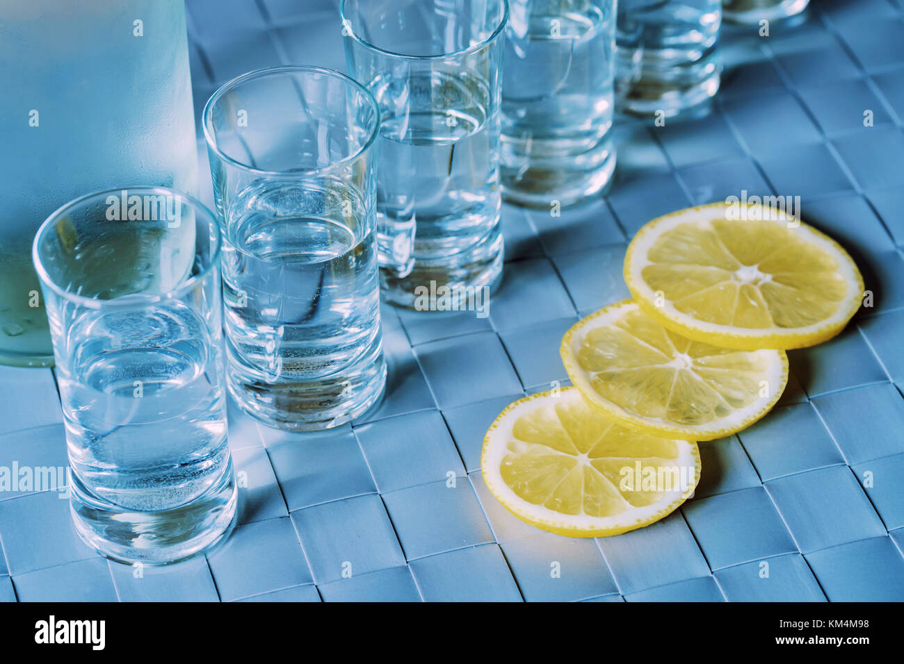 Vodka shot glass and lemon on blue surface - Stock Image