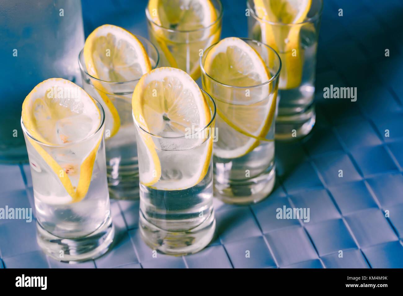 Vodka shot glass and lemon on blue surface - Stock Image