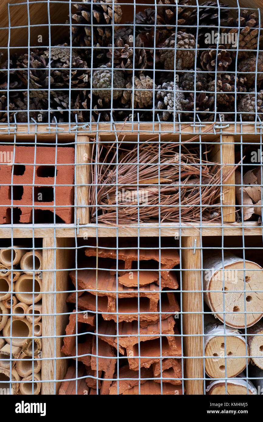 An insect hotel suitable for a variety of insects to nest or hibernate inside. - Stock Image