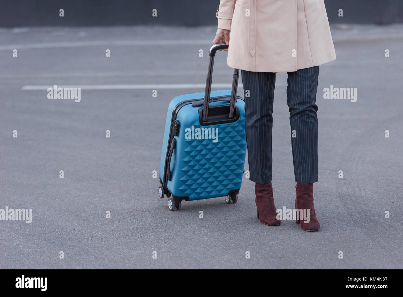 woman in trench coat with suitcase - Stock Image